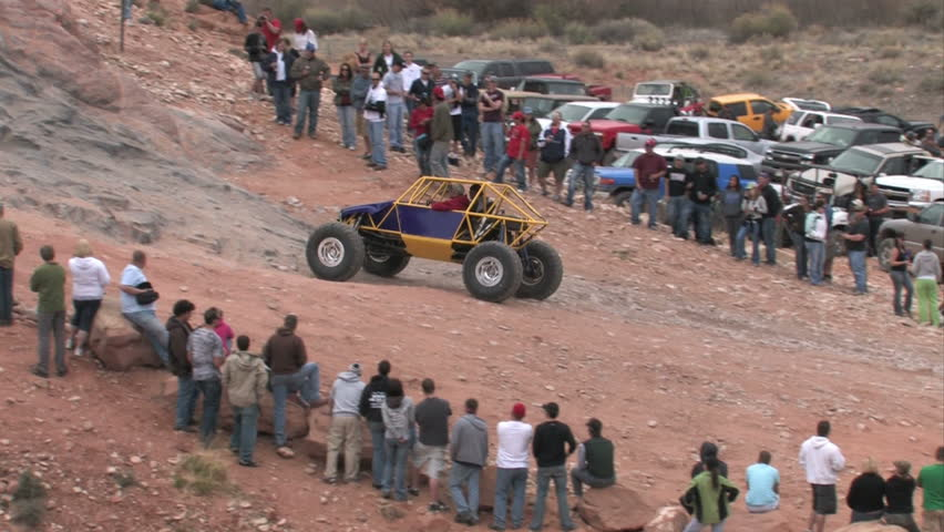 Moab Utah Jeep Safari. Potato Salad rock hill with spectators watching modified purple and yellow buggy climbing steep rock ledge.