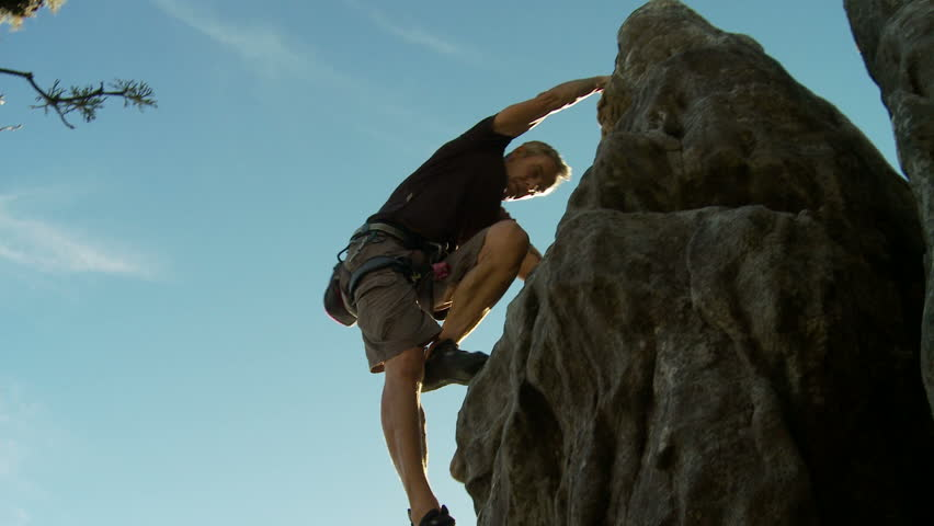 Rock climber scales a rock on Table Mountain, South Africa and takes in the view
