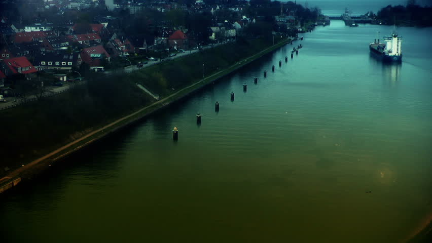 Cargo ship at sundown in Kiel Cannal, Germany, zoom out