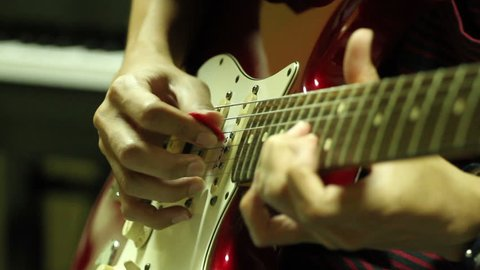 guitarist playing electric guitar in studio close up with shift focus