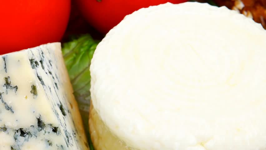 soft feta cheese with aged delicatessen cheeses on cutting wooden plate with tomatoes bread and olive oil