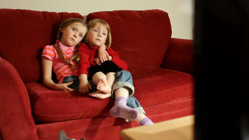 Two little sisters watching TV together on the sofa at home