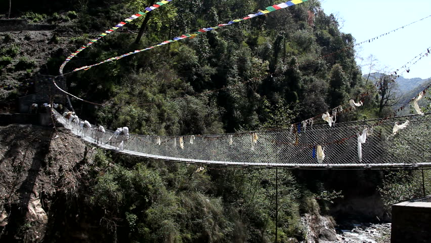Pony Train Crosses Remote Bridge In Himalayas. In remote parts of Nepal the only