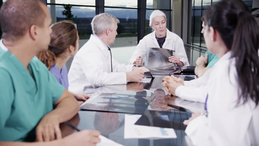 A diverse team of medical personnel are having a meeting in a light, modern private healthcare facility. They are discussing a patient's x-ray results and looking for a diagnosis. #3848765