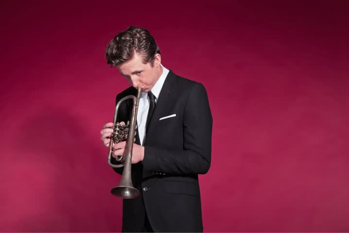 Retro 50s style male trumpet player in black suit. Studio shot against red background. Stop motion. Time lapse. No audio.