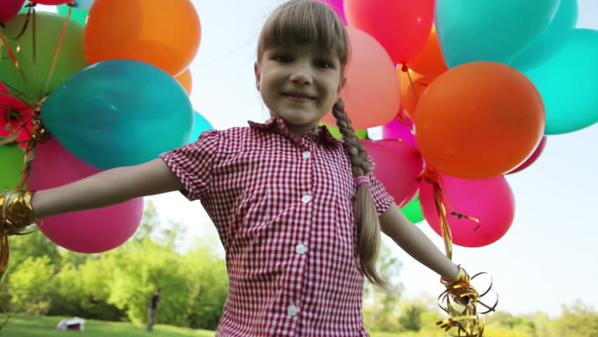 Child spinning with balloons in the park and looking at camera