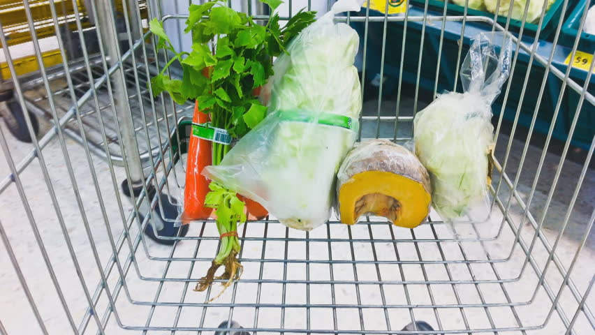 Closeup of female shopper with trolley at supermarket with healthy food.