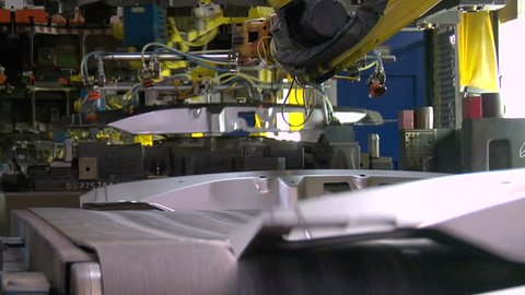 Sheet metal vehicle parts are stamped at the manufacturer and moved through an automated assembly line of robotic arms via conveyor belt in an automotive plant in Detroit.
