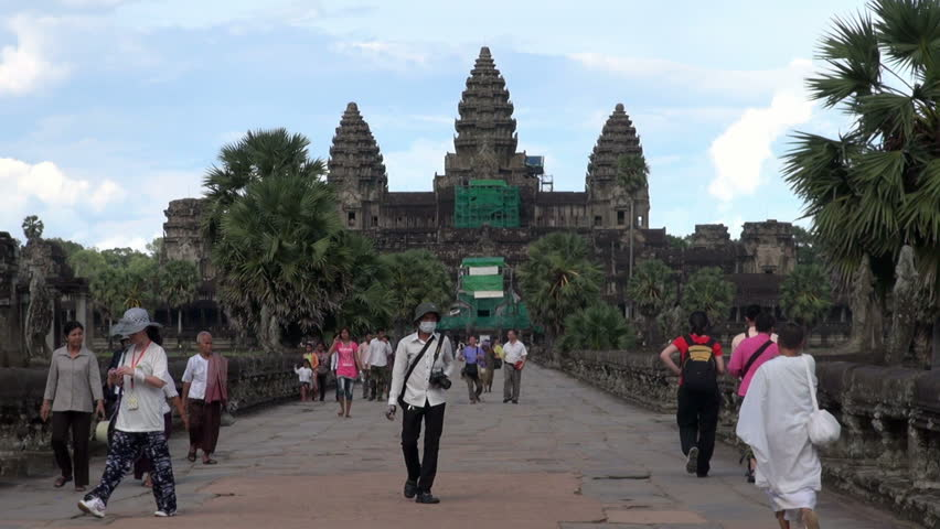 SIEM REAP, CAMBODIA - CIRCA JUNE 2011 - Tourists who visit Angkor Wat Temple walk at the main entrance.