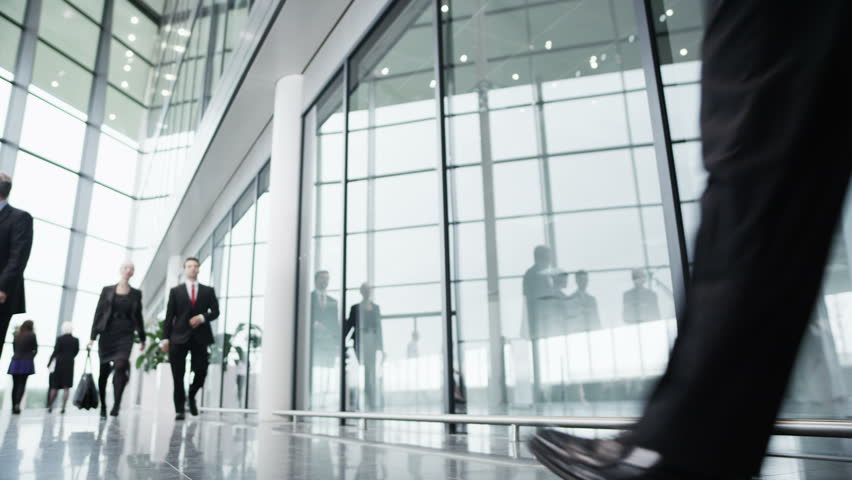 Diverse group of business people walking around a light and modern open plan office building.