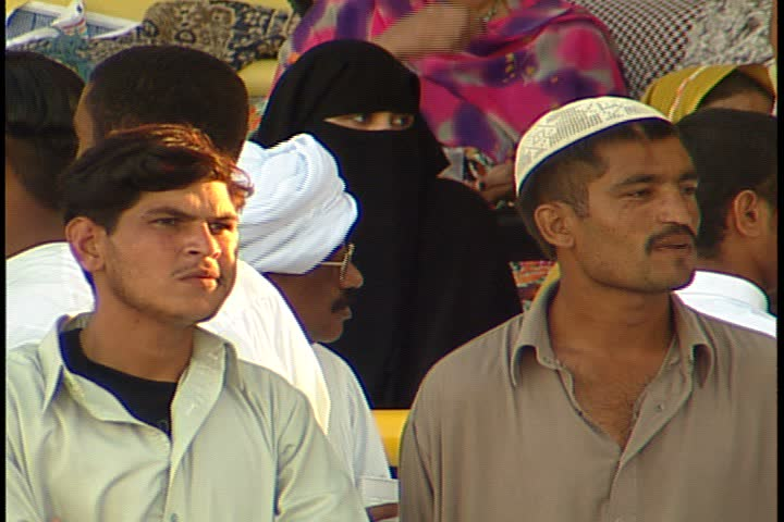 DUBAI - NOVEMBER 02, 2001: General views of Jebel Ali Race Course; MS two young Muslim men. Behind them is a women dressed in black niqab with only her eyes showing.