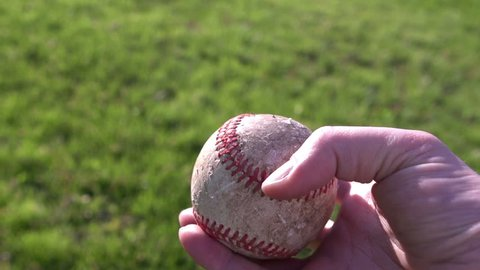 Walking with baseball in grass