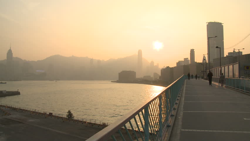 HONG KONG, CHINA - FEBRUARY 2012: Air pollution and choking smog cloak the skyline of Hong Kong as pedestrians walk on bridge at sunset. Shot in full HD 1920x1080 30p on Sony EX1.