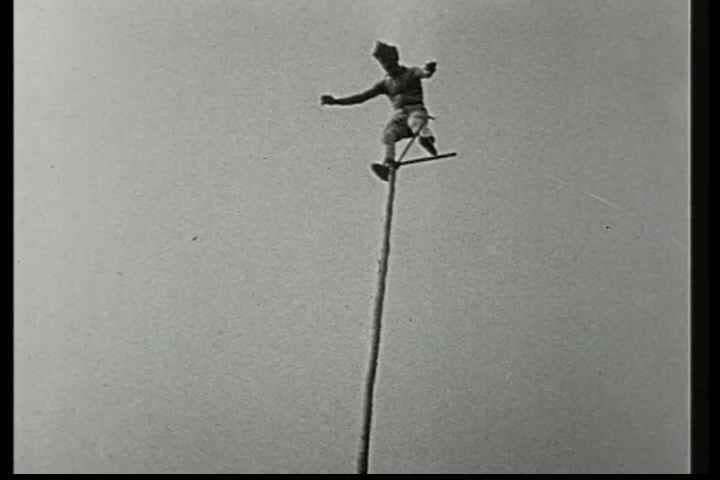 1920s - A man balances on a pole at a great height in this 1928 stunt film.