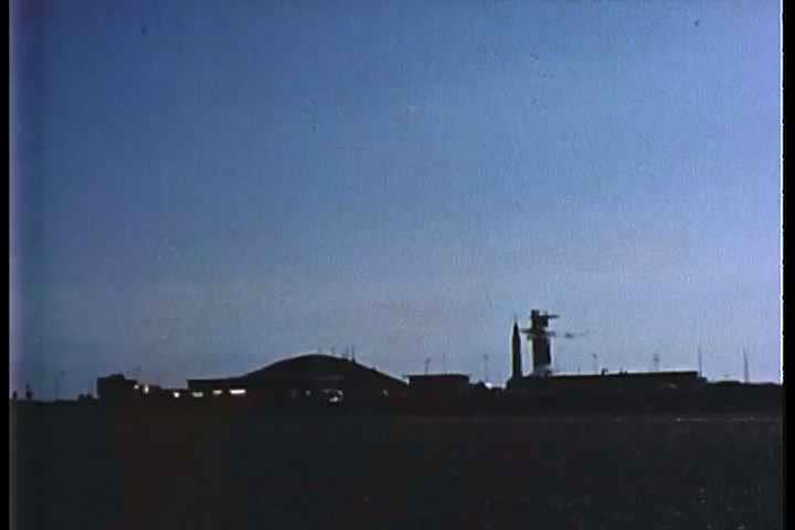 1960s - Military vehicles passing at dawn at a base.