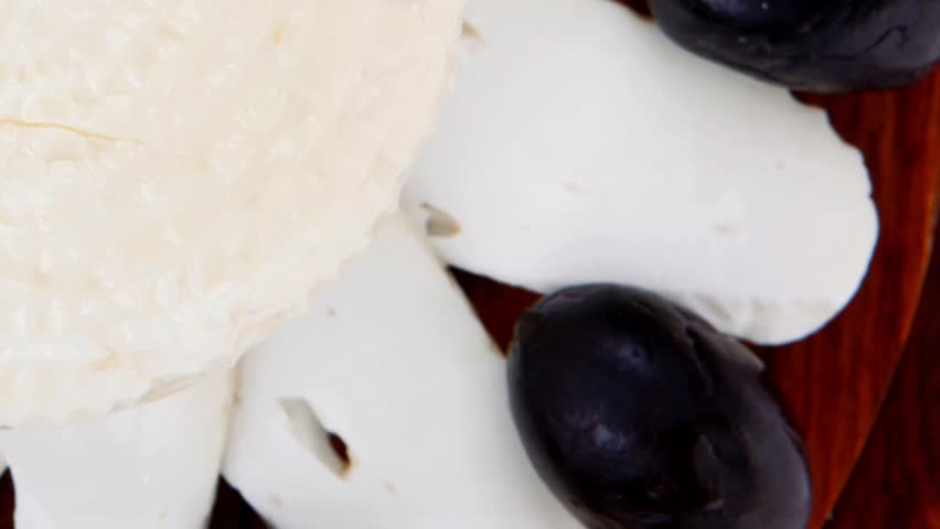 dairy products : feta white cheese sliced on cut board with olives and basil leaves 1920x1080 intro motion slow hidef hd