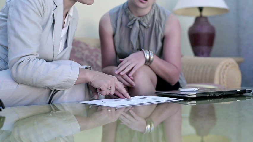 Two young businesswoman sitting in hotel lounge with laptop and documents