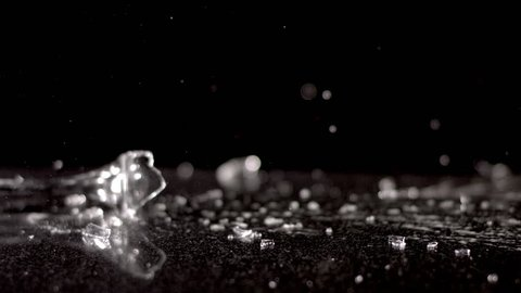 A champagne glass falls in slow motion against a black background. It shatters as it hits the ground, spilling its contents and sending shards of glass flying everywhere.