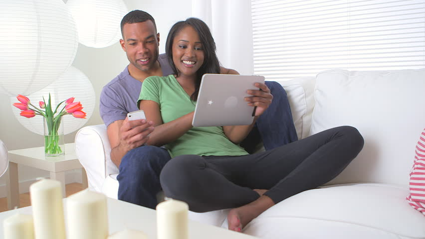 Black couple browsing the web on their mobile devices
