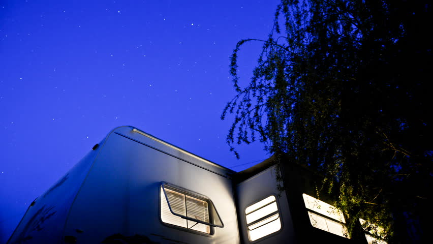 camper trailer from dusk to darkness as the stars come out and pass by overhead