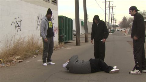 Great as B-roll for a piece of violence and gangs. A trio is beating a young male in a back alley, behind a building.
