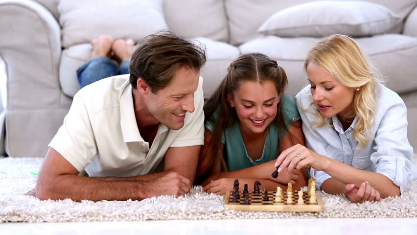 Parents and daughter playing chess on living room floor