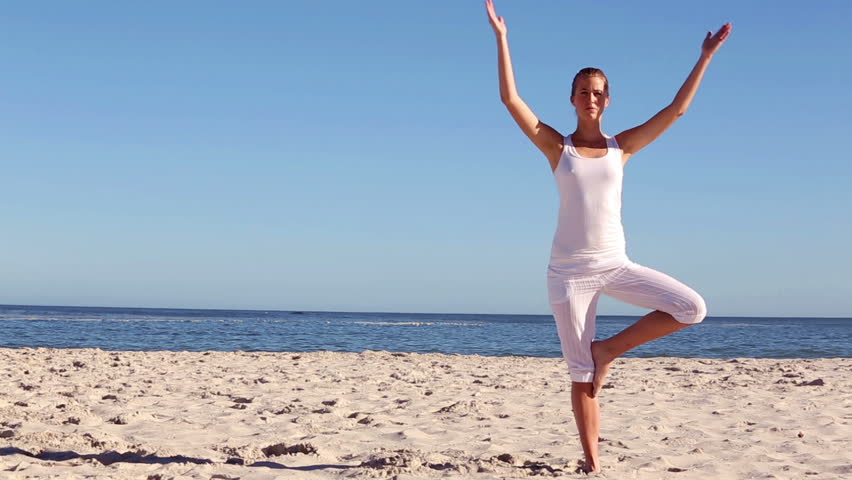 Woman practicing yoga on a beautiful sunny beach