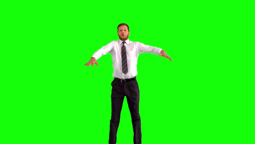 Businessman jumping and stretching his body towards the camera on green screen in slow motion