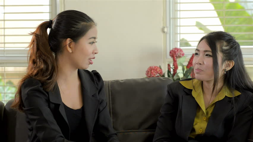 61a9ecaf8d6 Two young Asian women in business attire sitting on a sofa chatting.