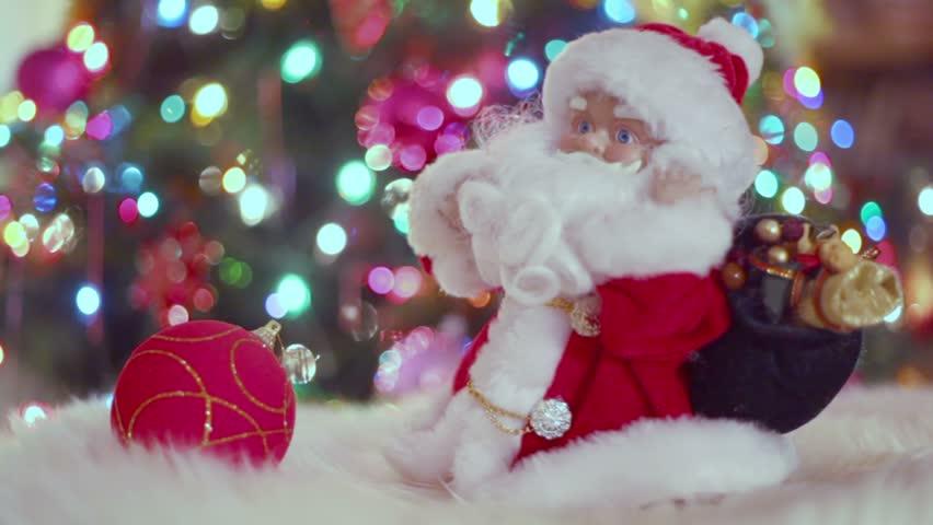 Miniature toy Santa Claus dances near Christmas tree with garland