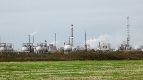 Industrial zone with factory and pipes which emit smoke near grass field at cloudy day