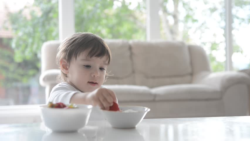 Sweet baby eating his first strawberry at living room