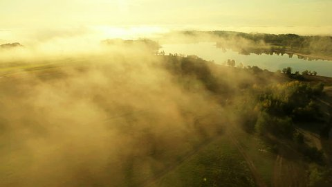 Aerial View. Flying over the beautiful river in clouds . Aerial camera shot. Sunrise. Landscape panorama. Altai, Siberia.