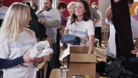 As charity workers and members of the community work together filling boxes with food and clothing, one female volunteer comes to the front of the shot and smiles directly at the camera. Slow motion.