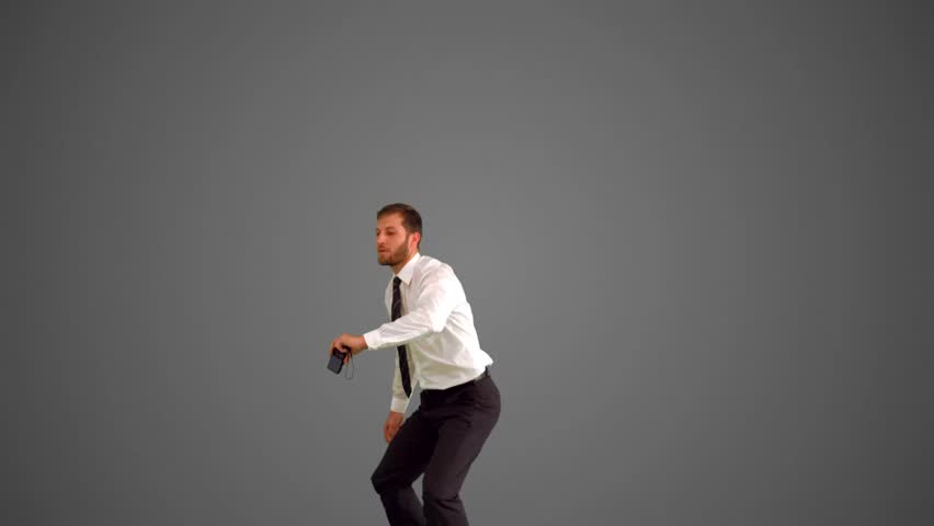 Businessman leaping and taking self portrait on grey background in slow motion