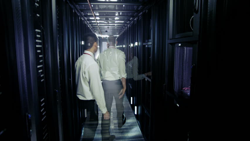 Two men of mixed ethnicity are working in a data center with rows of server racks and supercomputers. They are checking the equipment and discussing their work.