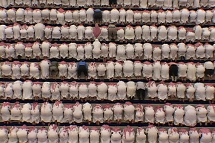 RIYADH, SAUDI ARABIA - OCTOBER 01, 2002: Overhead view of university mosque. Hundreds of men dressed in white, with red and white checked keffiyeh, standing and bowing in unison. | Shutterstock HD Video #4065628
