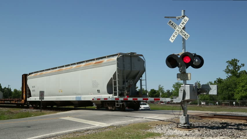 OLD TOWN SPRING, TEXAS/USA - MAY 8: Freight train passes railroad crossing, barrier rises and cars cross railroad track on May 08, 2013 in Old Town Spring. Texas Historic 1900s railroad town.