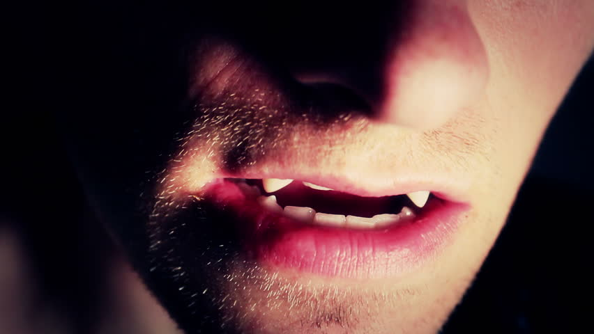 Man with scary fangs gets close to the camera.
