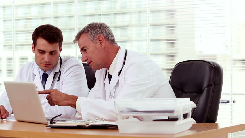 Doctor showing and explaining something to his colleague on a laptop