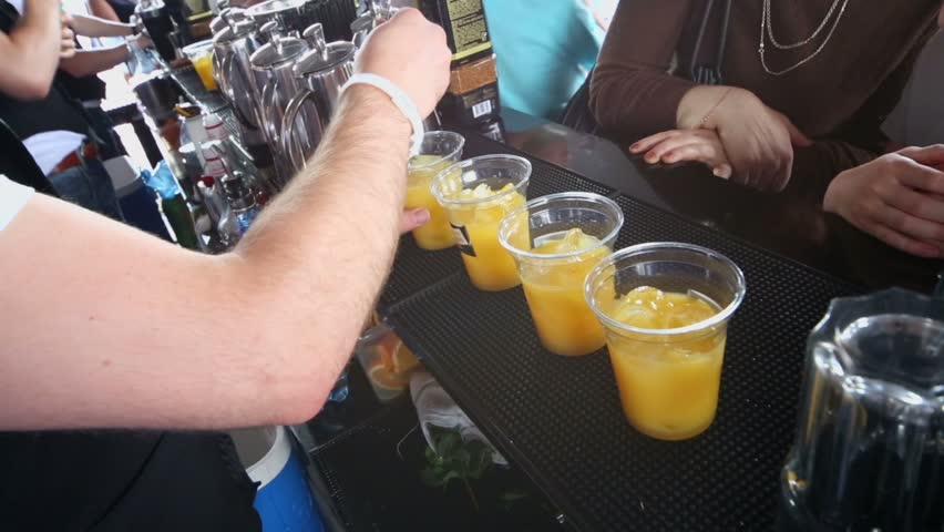 Bartender mixes cocktails with orange juice on bar counter with people stand near