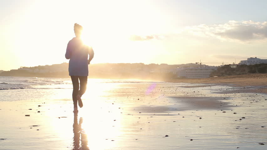 Man and woman jogging on the beach during sunset