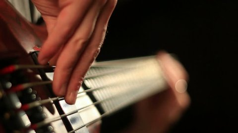 Close-up of hands of a bass guitar player. Find similar clips in our portfolio.