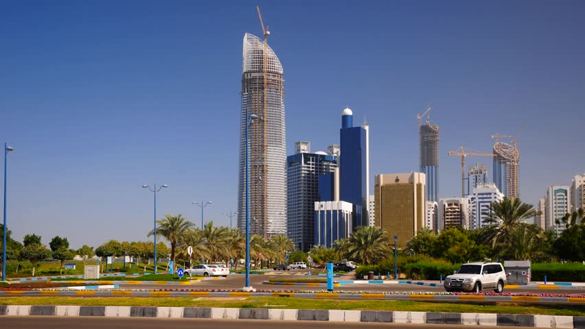 ABU DHABI, UNITED ARAB EMIRATES - CIRCA 2011 - The Corniche Skyline, Skyscrapers, both newly built and under construction. Traffic hurries past in foreground. TIME LAPSE