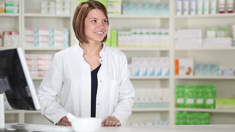 Young female pharmacist with customer at pharmacy