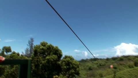 female takeoff and ziplines over tropical mountainous terrain