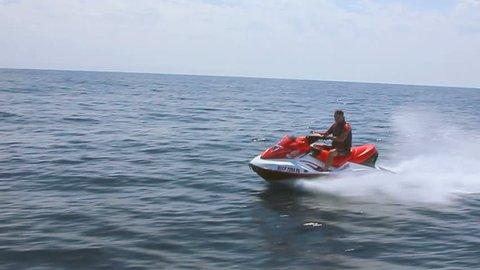MAN ON A JET SKI.  A man cruises the ocean on a jet ski.
