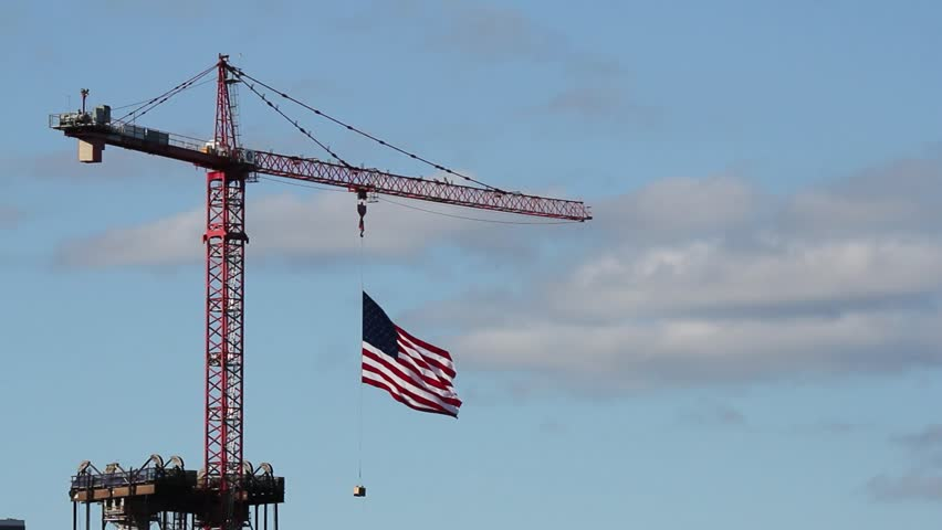 American Flag Flying High on Construction Crane on July 4th Independence Day against Blue Sky and Clouds 1920x1080