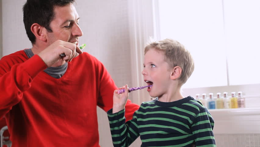 Father with son in brush teeth together in bathroom