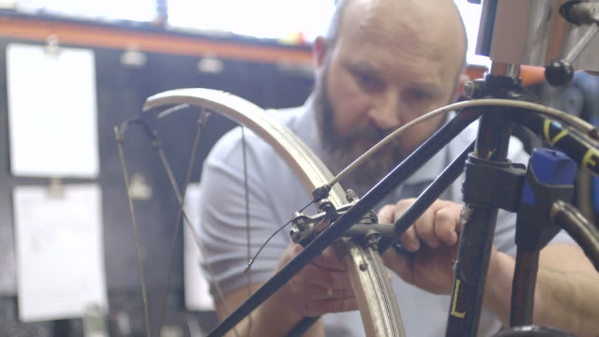 Man tightening bicycle wheel